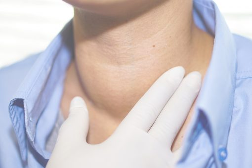 medical staff checking lump on woman's throat