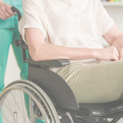nurse pulling wheelchair with old man sitting in it